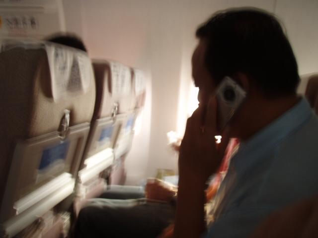 飛行機内で電話する人