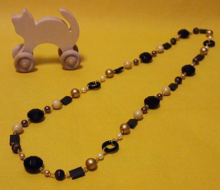 黒いプラスチックリングとゴールドのネックレス