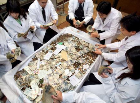 集まったさい銭を集計する銀行員