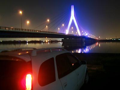 青い光でライトアップされた芦田川大橋とカリブ