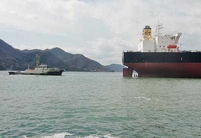 巨大船を引くタグボート