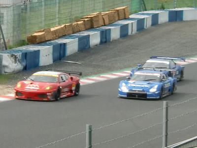 パイパーコーナーからレッドマンコーナーの直線でGT300クラスのフェラーリをパスするCALSONIC GT-R