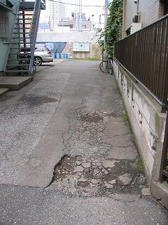 塀の横の道路面が大きく陥没し、雨が降ると、大きな水溜りが、