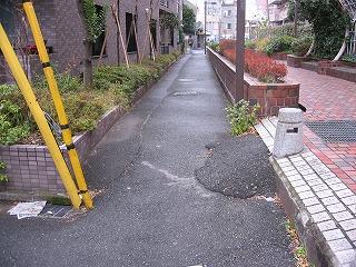 細い私道の入り口に東京電力の電柱のささえワイヤーが