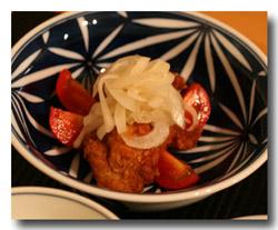 唐揚げの上に、玉ネギの甘酢漬けとトマト