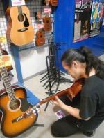楽器店「オオサカヤ」のギターを弾くg村山義光氏