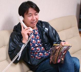 電話取材中の小曽根さん