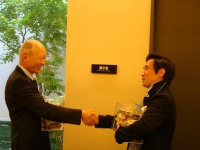募金箱を持ちながら握手をする角社長と監督