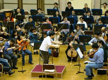 奏者に身体を向けて指揮するマエストロ