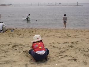 浜辺で砂遊びをする第一子